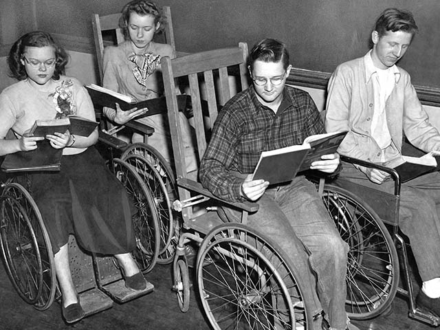 students in wooden back wheelchairs