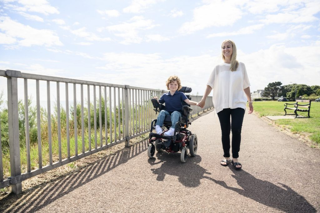 young child in wheelchair and walking companion