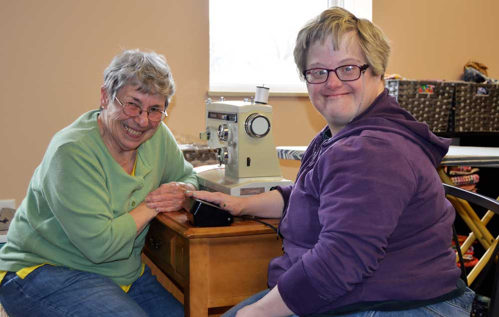 two women smiling at sewing machine