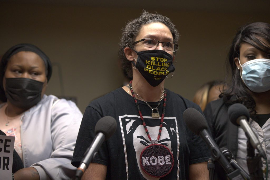 """A woman wearing a face mask with the text, """"Stop killing black people"""""""